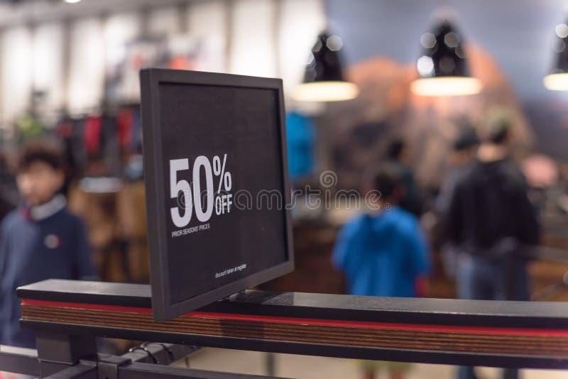 50 percenten van verkoopteken over kleren bij warenhuis met klant het winkelen royalty-vrije stock afbeelding