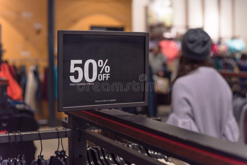 50 percenten van verkoopteken over kleren bij warenhuis met klant het winkelen royalty-vrije stock afbeeldingen