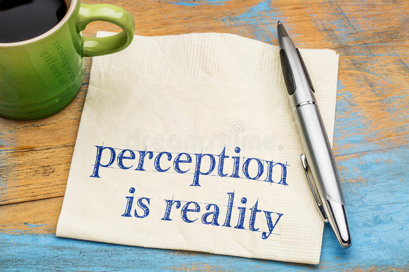 Perception is reality text on napkin. Perception is reality - handwriting on a napkin with a cup of espresso coffee stock image