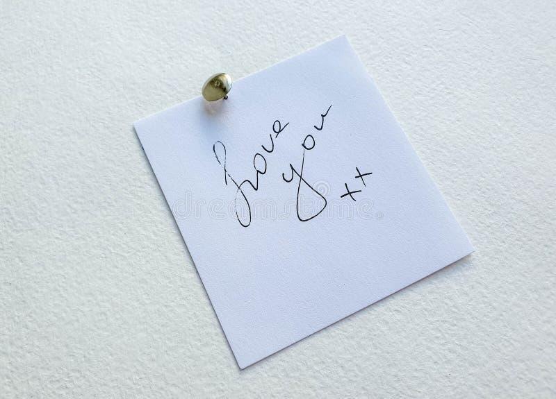Percevejo de prata do metal pequeno que guarda o anote com amor você texto no fundo branco Ame a mensagem fotos de stock royalty free