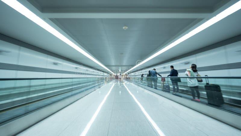Percez un tunnel à l'aéroport de Séoul avec des personnes sur l'escalator plat image libre de droits