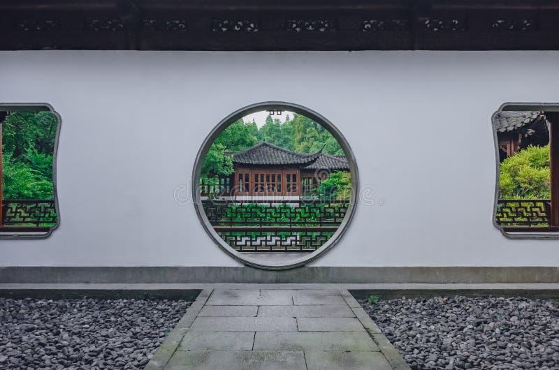 Percorso che conduce al portone della luna con la vista della costruzione del cinese tradizionale, in un giardino cinese, vicino  fotografia stock