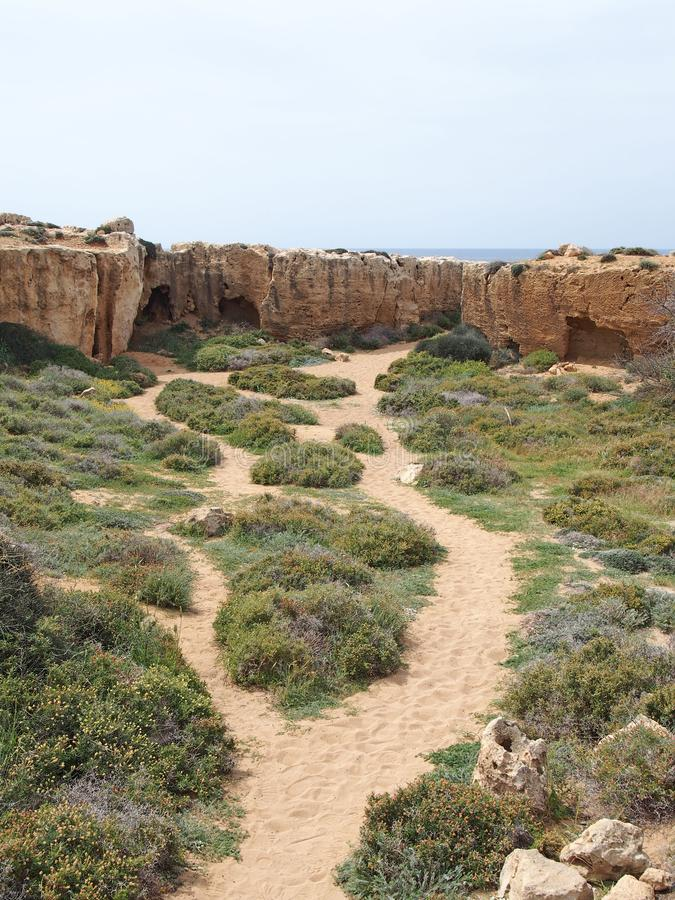 Percorso che conduce alle caverne ed alle tombe scolpite nella parete rocciosa vicino al mare alla tomba dell'area di re in papho immagine stock