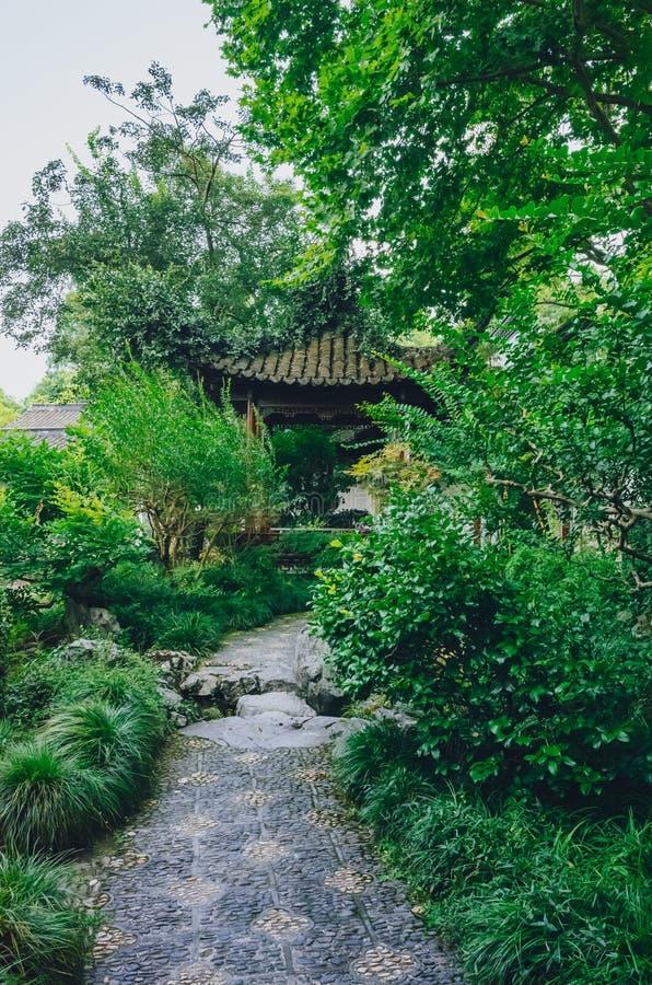 Percorso che conduce ugualmente un padiglione del cinese tradizionale fra gli alberi, in un giardino cinese, vicino al lago ad ov immagine stock