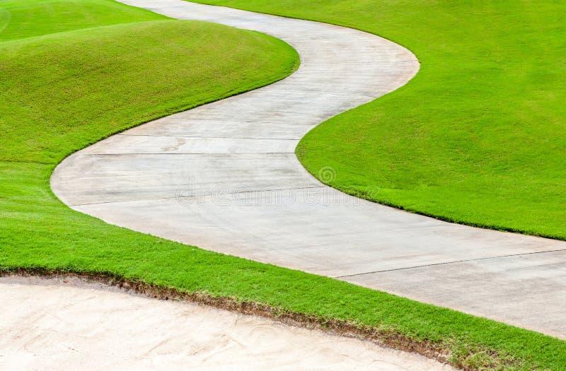 Percorso che curva attraverso l'erba verde nel campo da golf fotografia stock