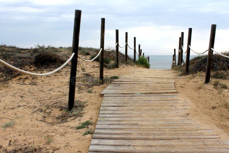 Percorso di legno alla spiaggia e un paesaggio isolato del mare della costa in un giorno nuvoloso fotografie stock libere da diritti