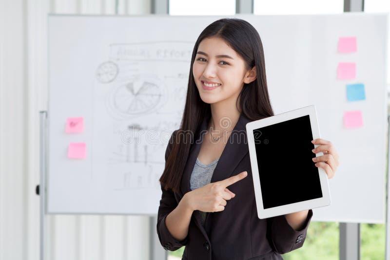 Percorso di ritaglio sullo schermo nero, donna di affari che indica dito e fotografia stock