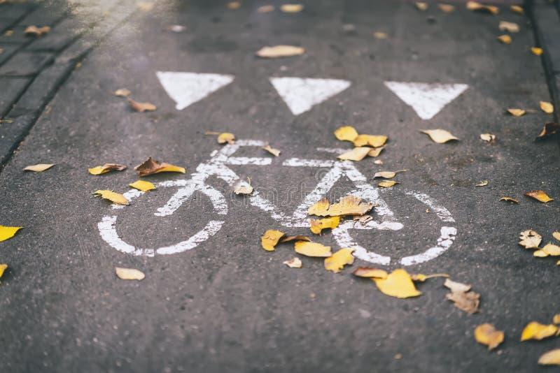 Percorso nella città, caduta della foglia, foglie sul marciapiede, bicicletta, segnale stradale di autunno della via immagine stock