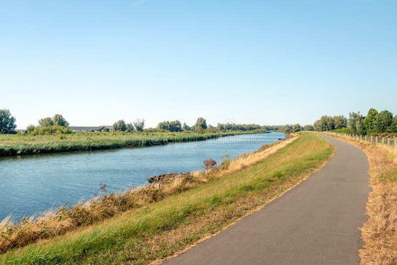 Percorso stretto della bici accanto ad un'ampia insenatura in una riserva naturale immagine stock