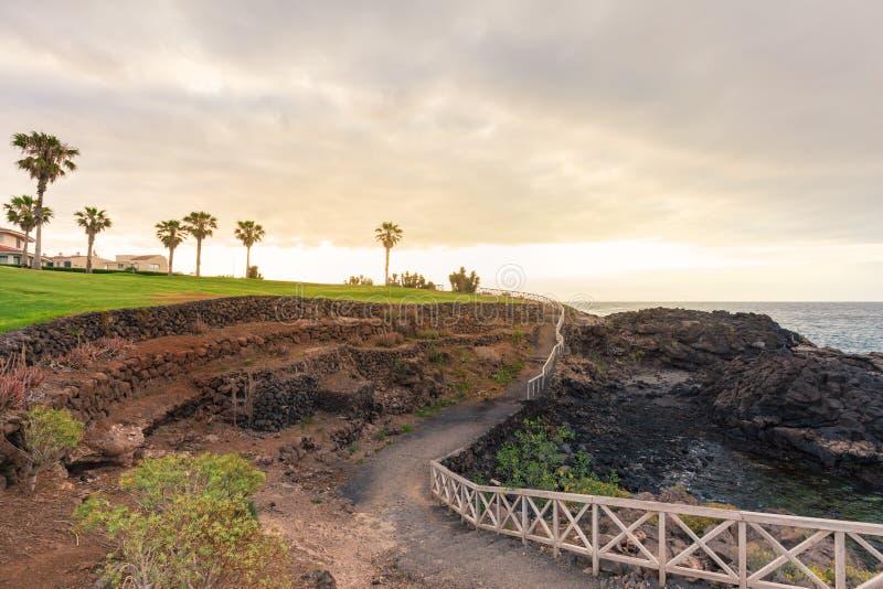 Percorso a terra con i corrimani lungo la linea costiera rocciosa fotografie stock libere da diritti