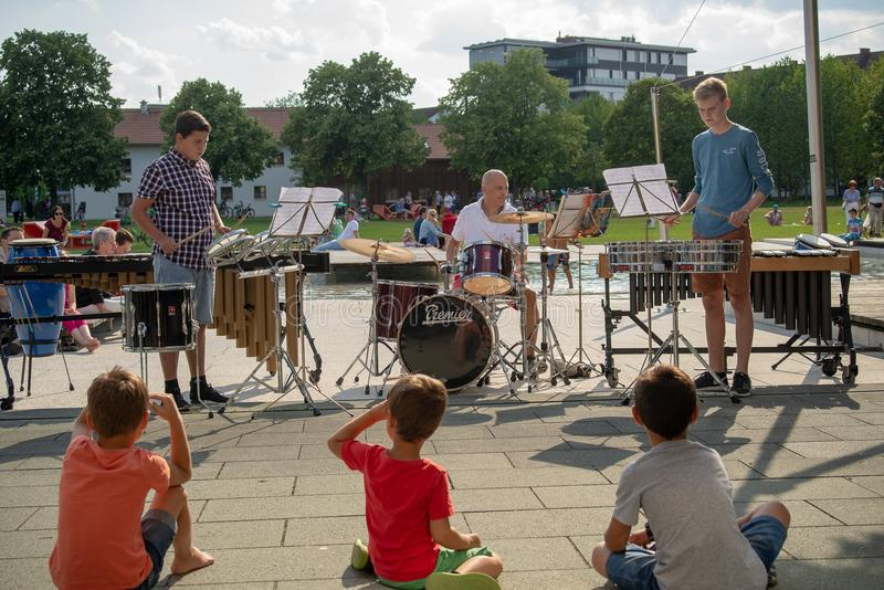 Percussion concert in a public park. Burghausen,Germany-June 16,2018 : Children look on during a music school`s public percussion concert in a park stock photos