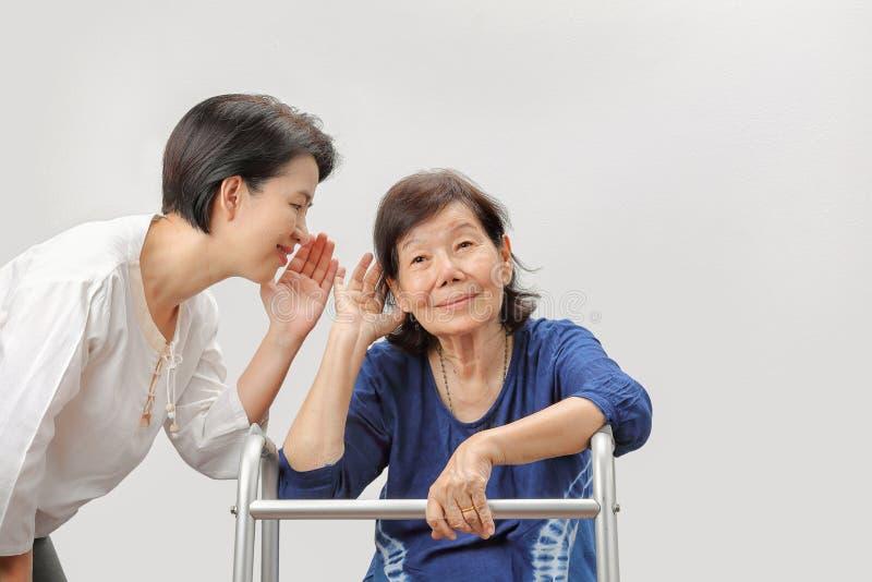 Perda da audição asiática da mulher dos sêniores foto de stock