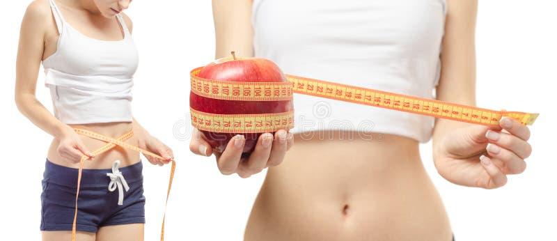 Perda de peso da perda de peso da jovem mulher com um centímetro e um grupo da maçã foto de stock royalty free