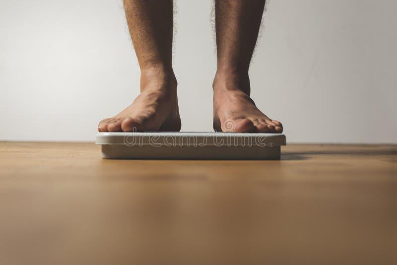 Perda de peso e conceito da dieta Posição do homem na escala imagem de stock