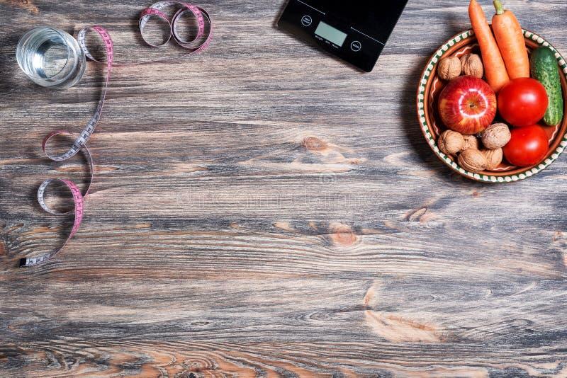 Perda de peso e conceito saudável comer Placa com os vegetais crus nela, em escalas da cozinha, na fita de medição e no vidro da  fotografia de stock royalty free