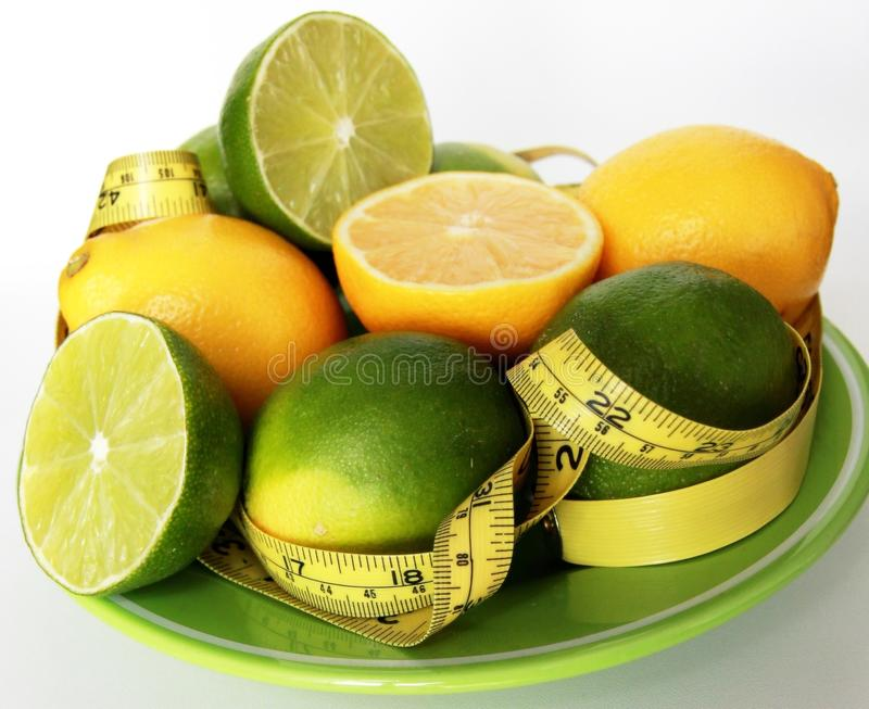 Perda de peso Fita de medição envolvida em torno dos limões fotos de stock royalty free