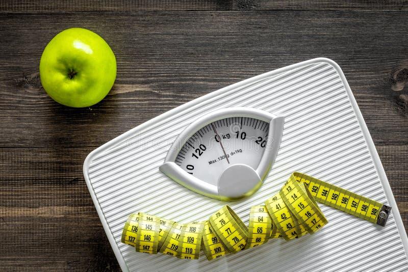 Perda il concetto del peso Bilancia pesa-persone, nastro di misurazione, mele sulla vista superiore del fondo di legno immagine stock libera da diritti