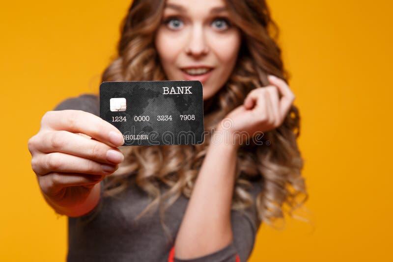 Perda-sul ritratto di giovane donna castana felice che tiene la carta di credito ed i sacchetti della spesa variopinti, esaminant fotografie stock libere da diritti