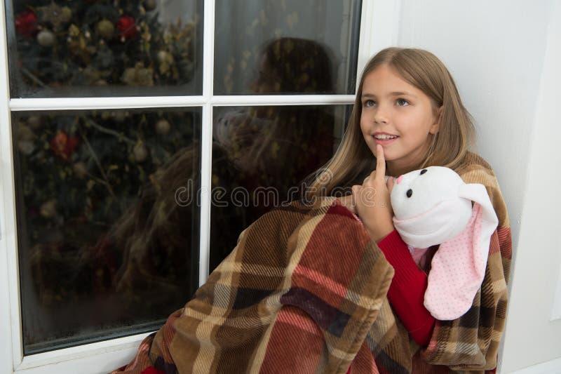 Perdido en pensamientos Poco niño se relaja el Nochebuena Pequeño niño con el juguete del conejito en la ventana Pequeño amigo de fotografía de archivo