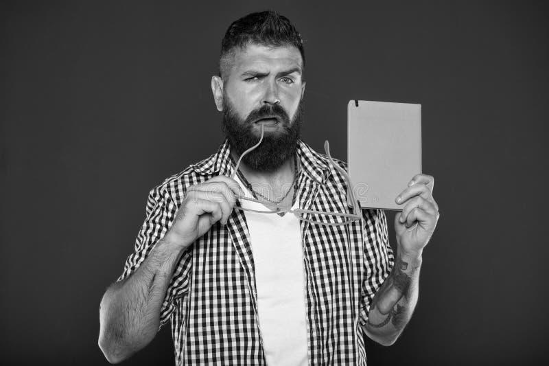 Perdido en sus pensamientos Empoll?n del libro que sostiene los vidrios de lujo Estudiante masculino de la universidad con las no fotos de archivo libres de regalías