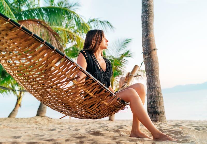 Perdido na menina de sonhos que senta-se na rede entre palmeiras na praia tropical da ilha fotografia de stock