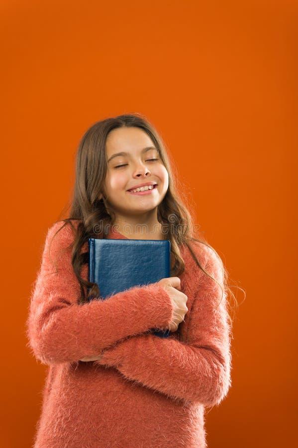 Perdido no conto de fadas Fundo alaranjado do livro da posse da menina Livro do abraço da criança Conceito das livrarias Livro li imagens de stock