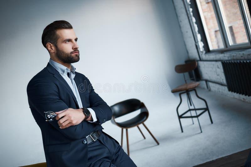 Perdido nos pensamentos O homem de negócios bem vestido no terno à moda está olhando de lado pensativamente em um escritório mode foto de stock