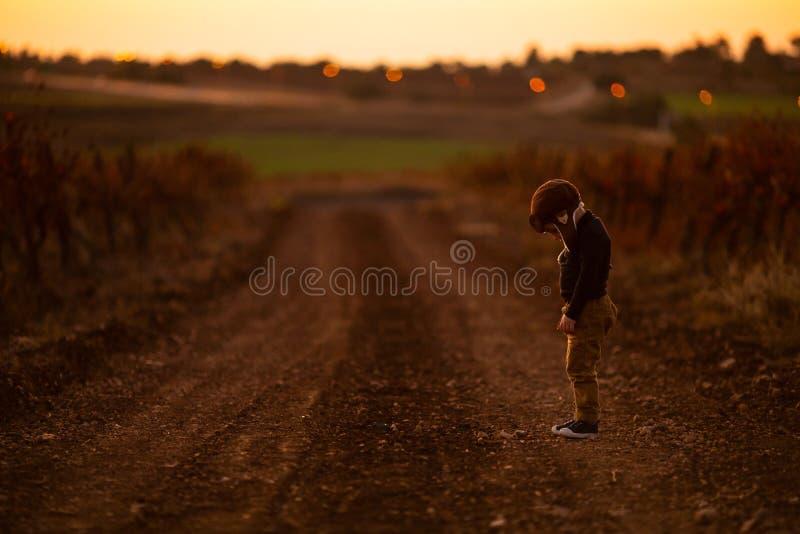 Perdieron al niño pequeño y había uno cerca de camino en el otoño imagen de archivo libre de regalías