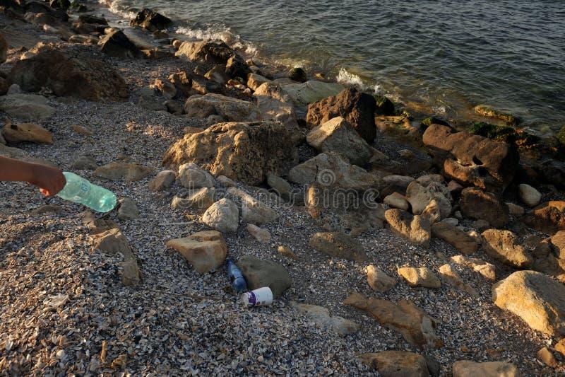 Perdon som kastar en flaska av vatten på kusten som förorenar miljön royaltyfri fotografi