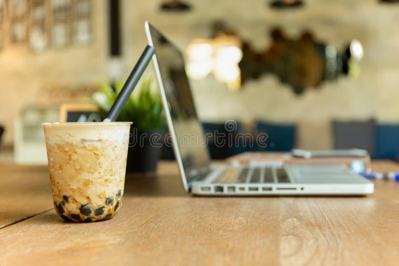 Perełkowy mleko zamrażał herbaty z laptopem na drewnianym stole w kawiarni fotografia stock