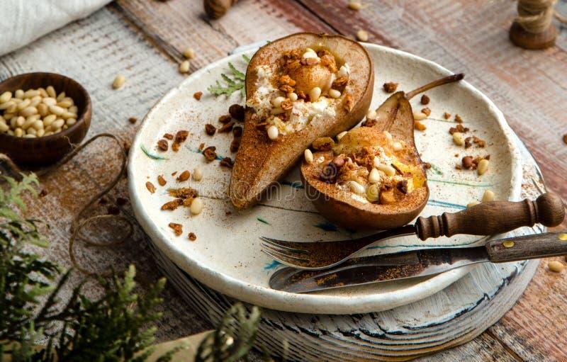 Pere al forno a metà con ricotta, granola, noci di pino su piastra di ceramica fotografia stock libera da diritti