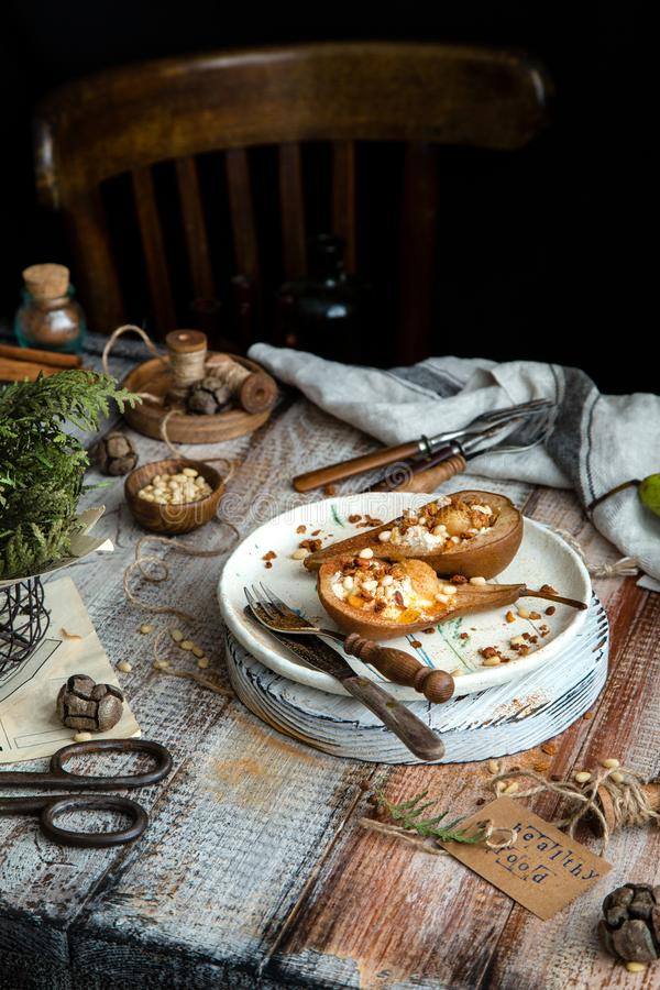 Pere al forno a metà con ricotta, granola, noci di pino su piastra di ceramica fotografia stock