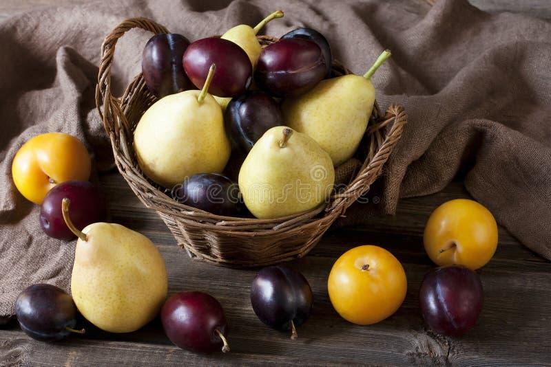 Pere e prugne deliziose su una tavola di legno rustica immagini stock