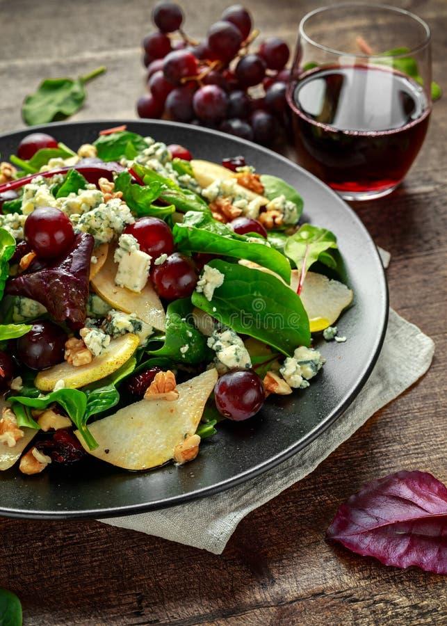 Pere fresche, insalata del formaggio blu con la miscela verde di verdure, noci, uva rossa Alimento sano immagini stock libere da diritti