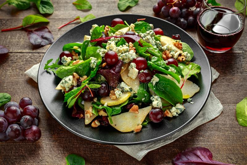 Pere fresche, insalata del formaggio blu con la miscela verde di verdure, noci, uva rossa Alimento sano fotografie stock