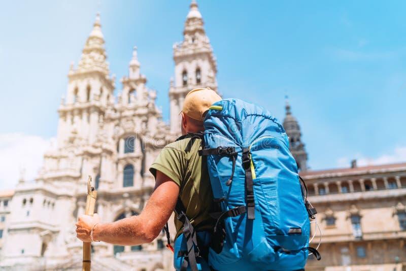 Peregrino do homem do mochileiro que olha a posição de Santiago de Compostela Cathedral na plaza do quadrado de Obradeiro - o qua fotos de stock royalty free