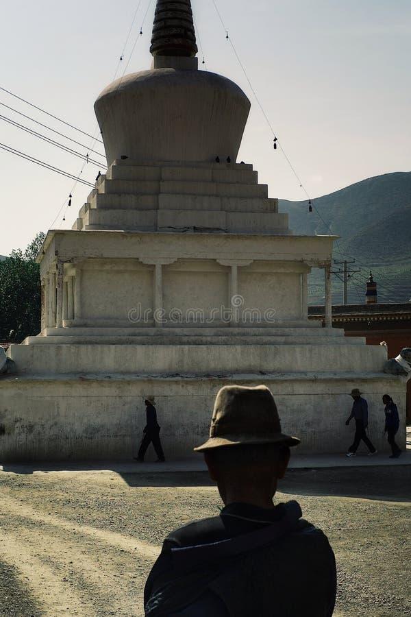 peregrinos budistas tibetanos que caminan alrededor de un stupa mientras que un hombre en un sombrero tradicional que los mira fotografía de archivo
