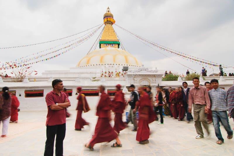 Peregrinos no identificados que caminan alrededor del stupa de Bodhnath en Katmandu, Nepal foto de archivo