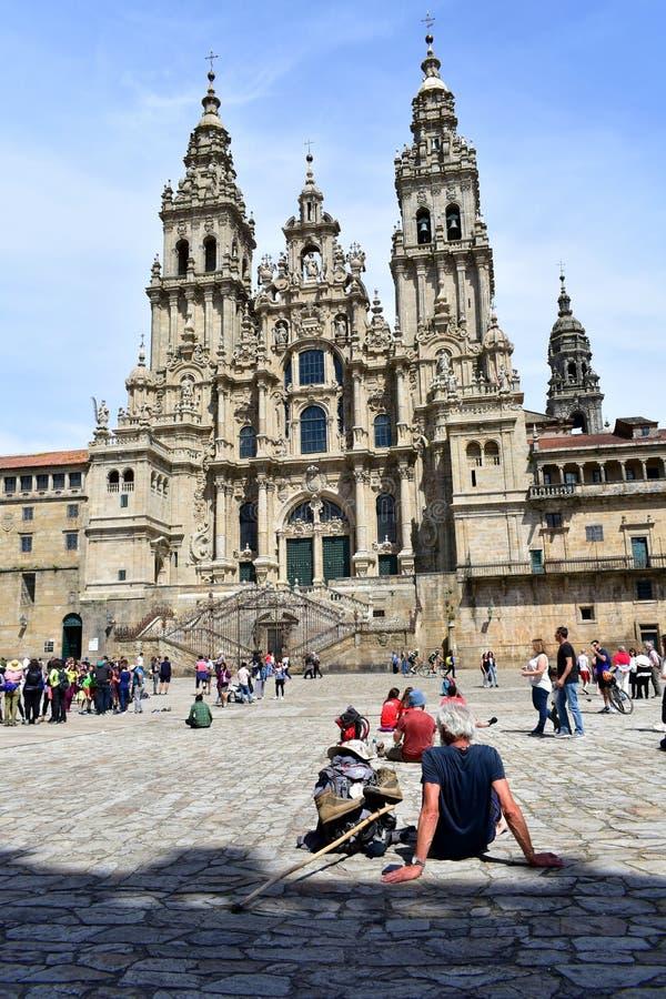 Peregrinos que descansam em Plaza del Obradoiro na frente da catedral Santiago de Compostela, Espanha, o 5 de maio de 2019 imagem de stock