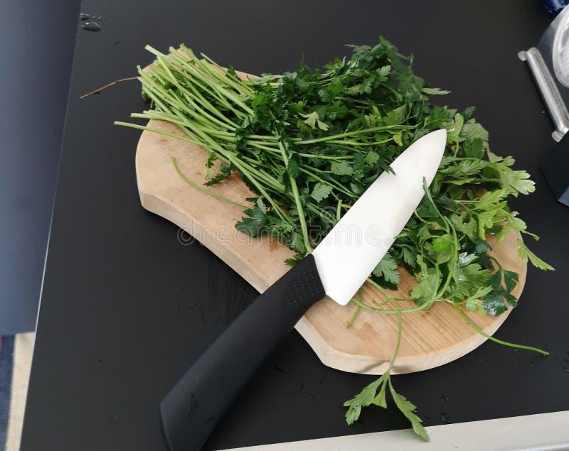 Perejil en el cortador en la cocina imagen de archivo
