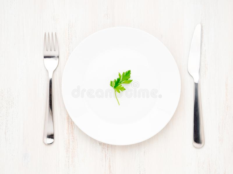 Perejil en la placa, la bifurcación y el cuchillo blancos vacíos en una tabla de madera blanca, visión superior, concepto de la d imagenes de archivo