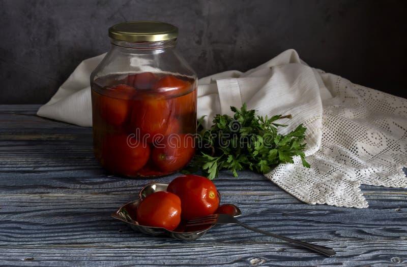 Perejil y tomates conservados en vinagre en una tabla de madera foto de archivo