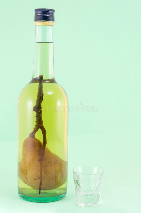 Perenbrandewijn met peer in de fles stock foto