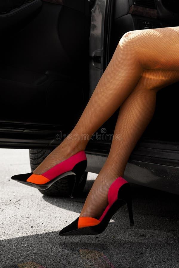 Perfeccione las piernas femeninas en medias y tacones altos en coche foto de archivo
