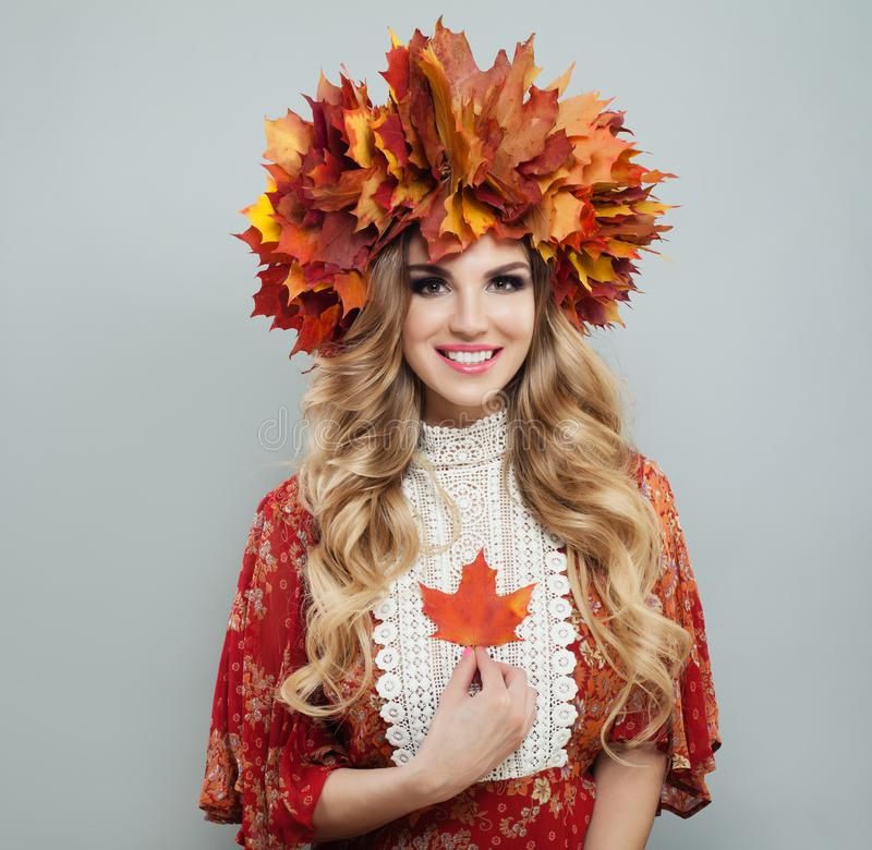 Perfect autumn woman in bright fall leaves crown holding red maple leaf stock photos