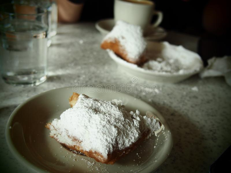 The Perfect Beignet in New Orleans. A perfect beignet covered in powdered sugar at Cafe Du Monde in the French Quarter of New Orleans stock photo