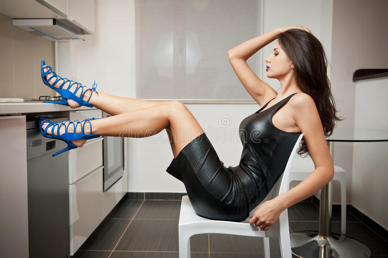 Perfect body woman in short tight fit leather dress and blue shoes posing relaxed in a modern kitchen. Side view of sensual woman. Perfect body woman in short royalty free stock photos