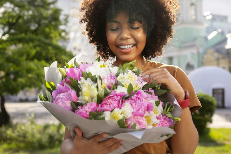 Happy curly woman looking at bouquet of flowers royalty free stock photo