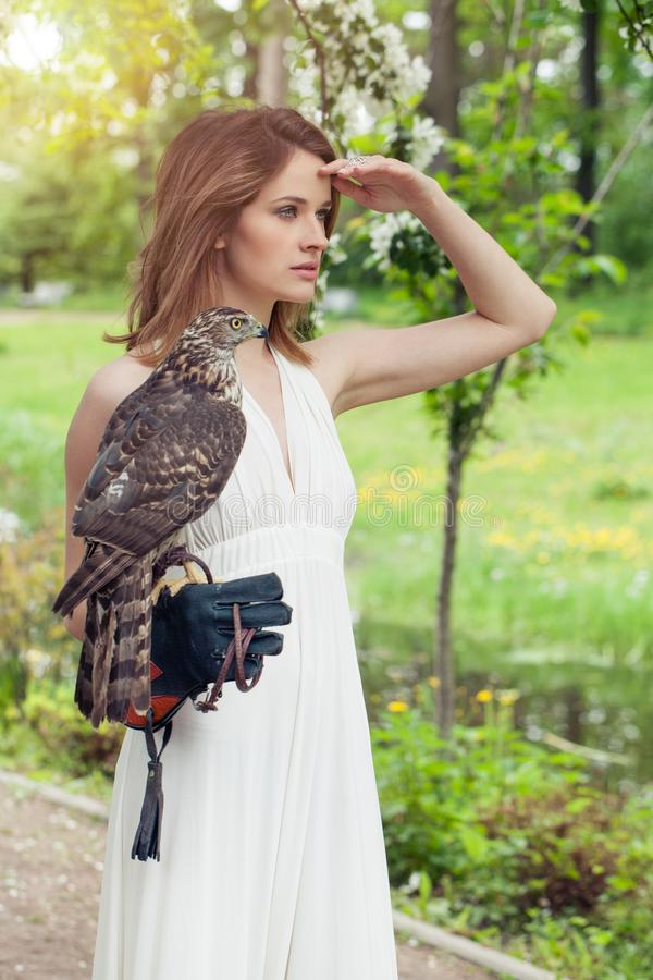 Perfect bride woman in white dress holding bird outdoor.  stock images