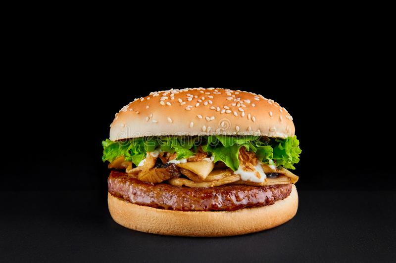 Perfect burger with beef cutlet, mushrooms, lettuce isolated at black background. Copy space stock image